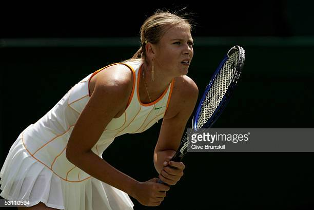 Maria Sharapova of Russia prepares to return serve against Nuria Llagostera Vives of Spain during the first round of the Wimbledon Lawn Tennis...