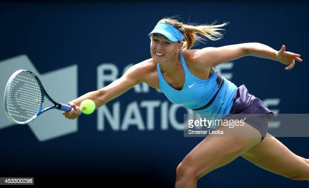 Maria Sharapova of Russia returns a shot to Carla Suarez Navarro of Spain during the Rogers Cup at Uniprix Stadium on August 6 2014 in Montreal Canada