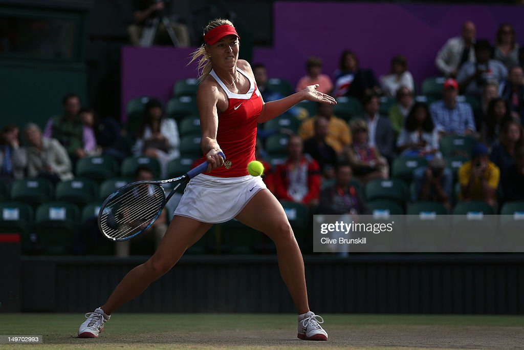 Maria Sharapova of Russia returns a shot to Kim Clijsters of Belgium during the Quarterfinals of Women's Singles Tennis on Day 6 of the London 2012 Olympic Games at Wimbledon on August 2, 2012 in London, England.