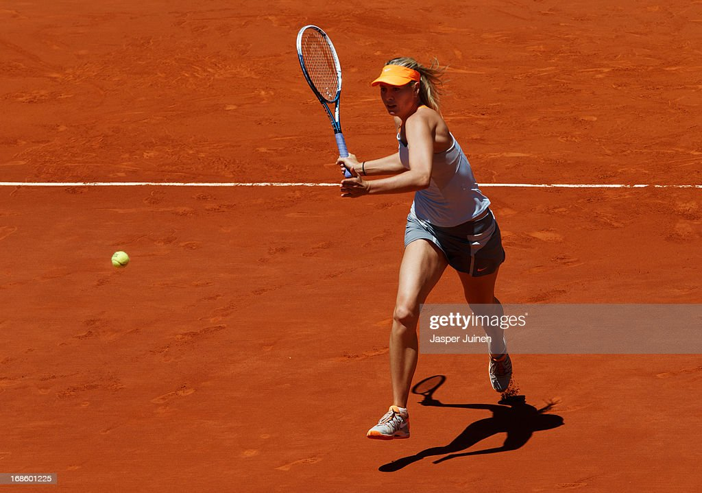 Maria Sharapova of Russia runs to play a backhand to Serena Williams of the US during the final match on day nine of the Mutua Madrid Open tennis tournament at the Caja Magica on May 12, 2013 in Madrid, Spain.