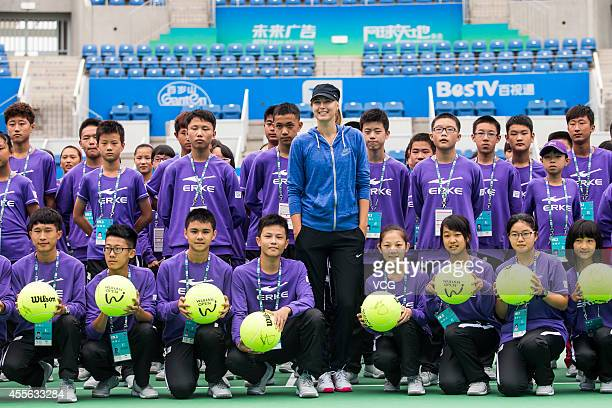 Maria Sharapova of Russia signs autographs for ball boys ahead of the start of 2014 WTA Wuhan Open at Optical Valley International Tennis Center on...