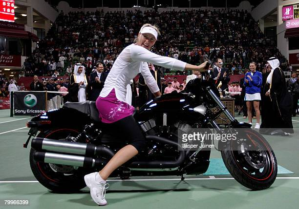 Maria Sharapova of Russia sits on a Harley Davidson motor bike she won after her final match against Vera Zvonareva of Russia on day seven of the WTA...