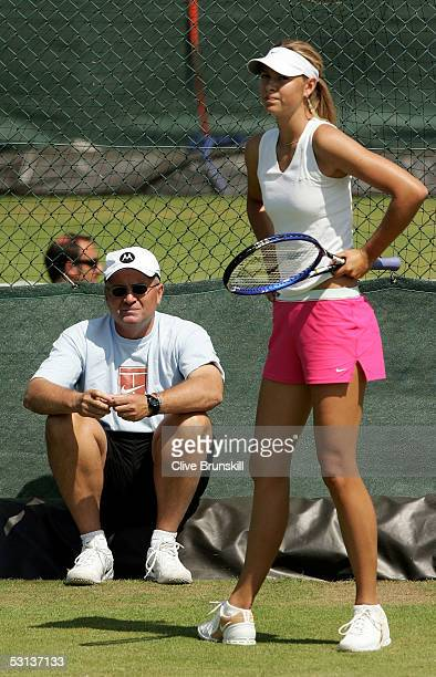 Maria Sharapova of Russia warms up as her father Yuri Sharapova gives his advice during the fourth day of the Wimbledon Lawn Tennis Championship on...
