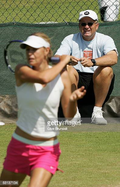 Maria Sharapova of Russia warms up as her father Yuri Sharapova watches on during the fourth day of the Wimbledon Lawn Tennis Championship on June 23...