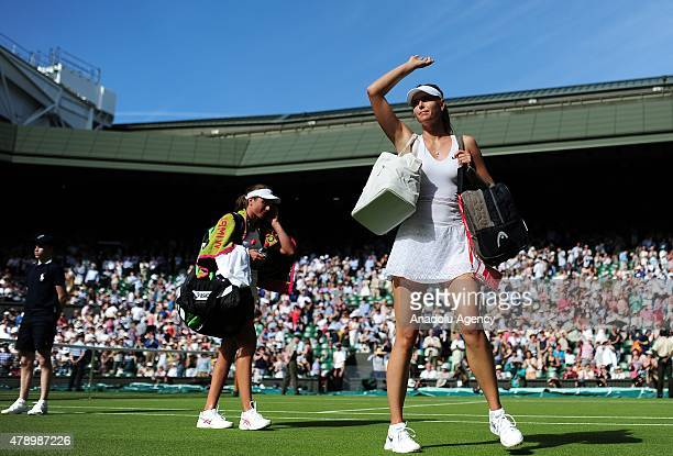 Maria Sharapova of Russia waves to the crowd as she leaves the court after victory against Johanna Konta of Great Britain during day one of the...