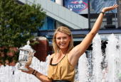 Maria Sharapova pose for photographers with the women's championship trophy outside of Arthur Ashe Stadium after winning the US Open at the USTA...