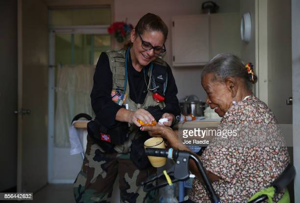 Maria Smith RN with the First Medical Relief team gives Rosario LugoLopez her medication as she receives medical care from the team at the Pedro...
