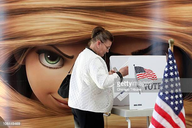 Maria Warmuz of Lemont Illinois finishes casting her vote at the AMC Woodridge 18 Theatres in front of the eyes of a huge poster promoting Disney's...