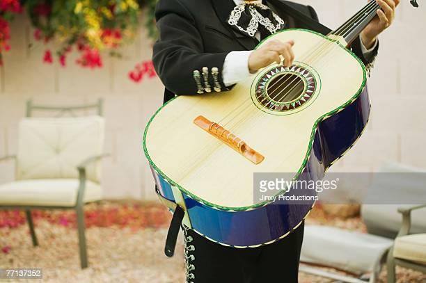 Mariachi band member holding guitar
