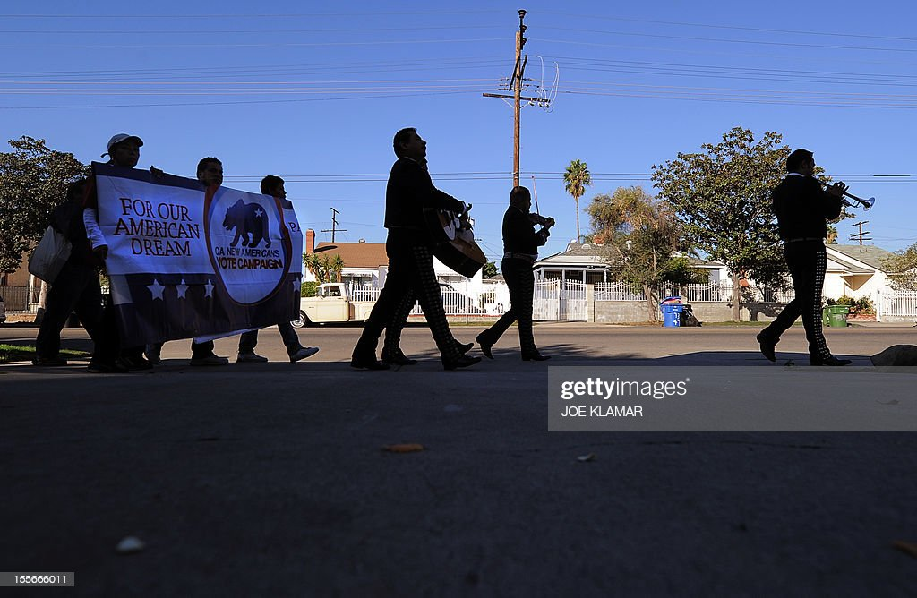 Mariachi musicians sing and play as they go from house to house to encourage people to come to vote on election day at the Sun Valley's Latino district, Los Angeles County, on November 6, 2012 in California.AFP PHOTO /JOE KLAMAR