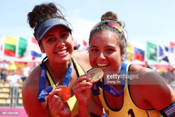 Mariafe Artacho and Taliqua Clancy of Australia celebrate with their medal after winning the final match against Kinga Kolosinska and Katarzyna...