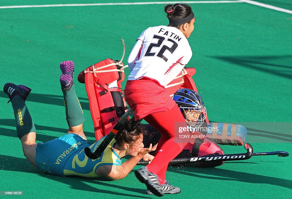 Mariah Williams (L) of Australia scores a goal past Malaysia's goalkeeper Farah Ayuni Yahya (R) and Fatin Naimah Zaki (C) during their women's Under 21's match at the International Super Series hockey tournament in Perth on November 22, 2012. Australia won 3-2. AFP PHOTO/TONY ASHBY -- IMAGE STRICTLY FOR EDITORIAL USE - STRICTLY NO COMMERCIAL USE