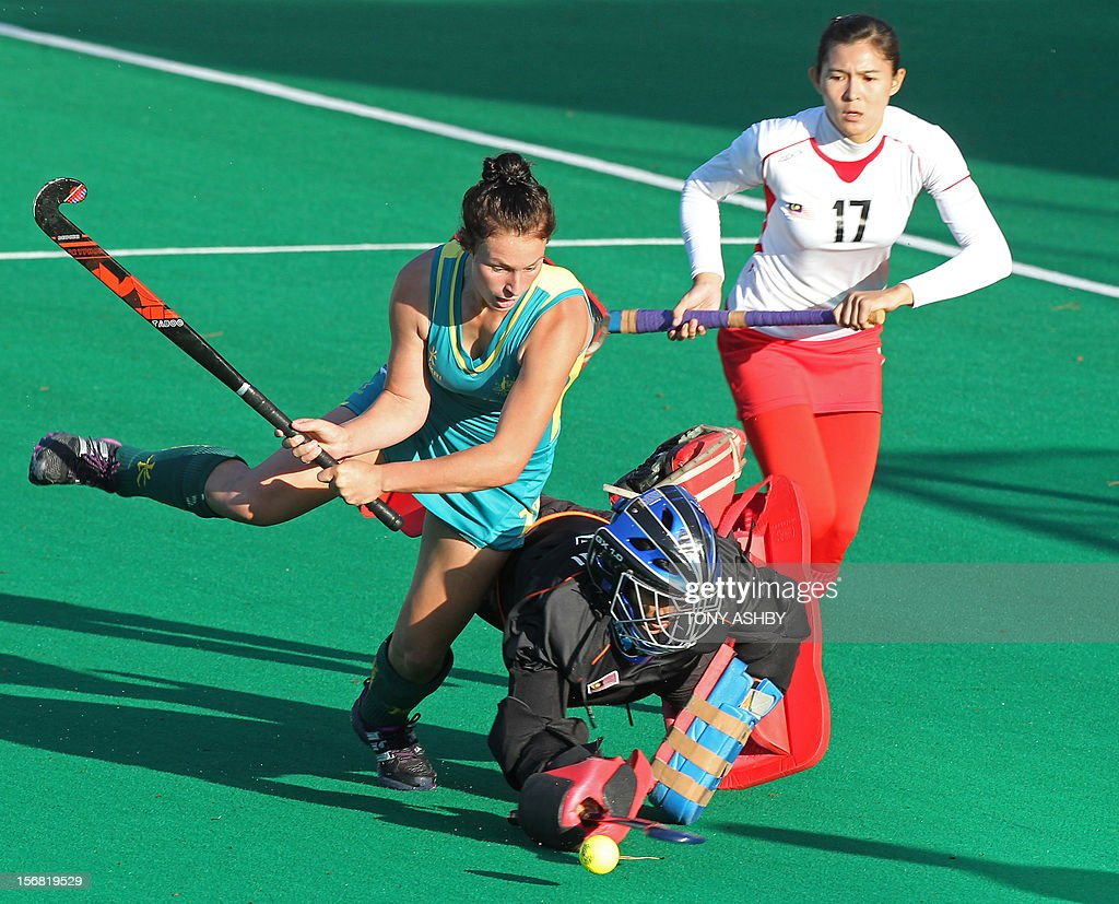 Mariah Williams (L) of Australia shoots for goal against Malaysian goalkeeper Farah Ayuni Yahya (C) during their women's Under 21's match at the International Super Series hockey tournament in Perth on November 22, 2012. Australia won 3-2.