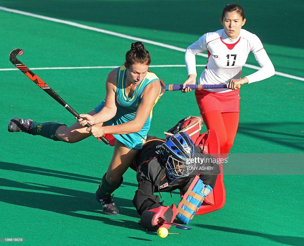 Mariah Williams (L) of Australia shoots for goal against Malaysian goalkeeper Farah Ayuni Yahya (C) during their women's Under 21's match at the International Super Series hockey tournament in Perth on November 22, 2012. Australia won 3-2.