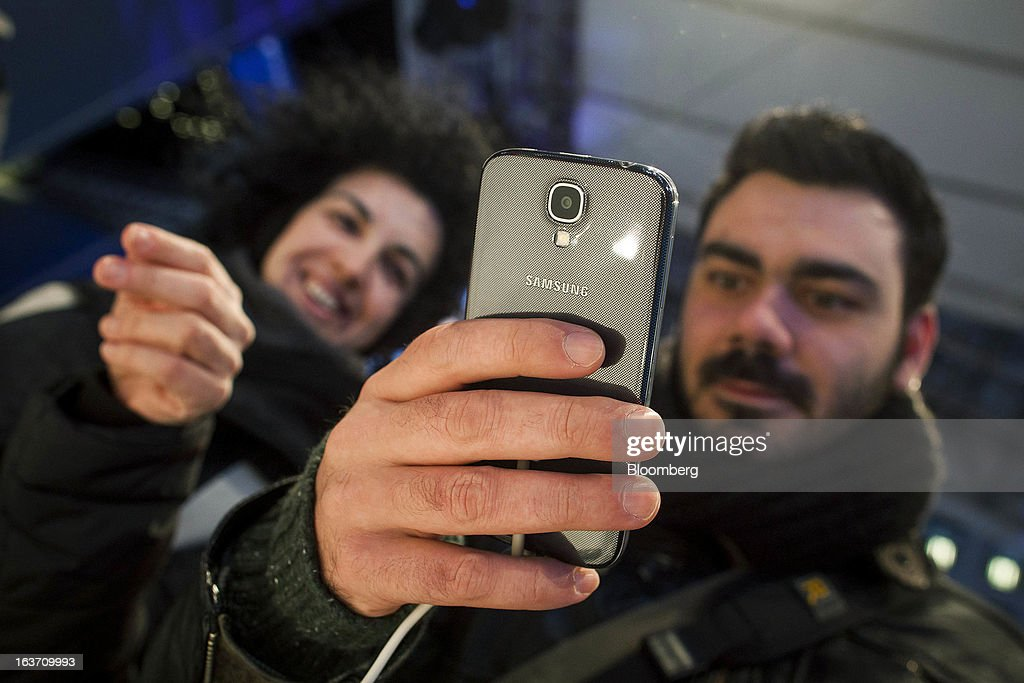 Mariajose Torres, left, and Aurelio Hernandez test out the new Samsung Electronics Co. Galaxy S4 smartphone during the Galaxy S4's release in Times Square in New York, U.S., on Thursday, March 14, 2013. Samsung Electronics Co. unveiled the Galaxy S4 with a bigger screen and software that tracks eye movements as the world's biggest smartphone seller takes its battle with Apple Inc. to the iPhone maker's home market. Photographer: Michael Nagle/Bloomberg via Getty Images