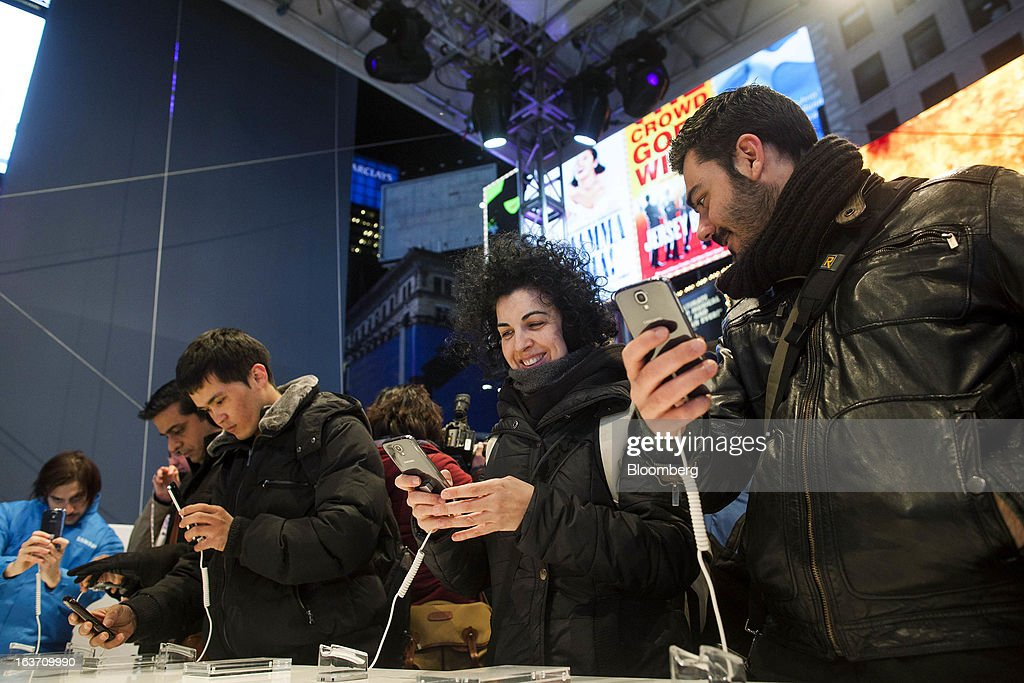 Mariajose Torres, second right, and Aurelio Hernandez, right, test out the new Samsung Electronics Co. Galaxy S4 smartphone during the Galaxy S4's release in Times Square in New York, U.S., on Thursday, March 14, 2013. Samsung Electronics Co. unveiled the Galaxy S4 with a bigger screen and software that tracks eye movements as the world's biggest smartphone seller takes its battle with Apple Inc. to the iPhone maker's home market. Photographer: Michael Nagle/Bloomberg via Getty Images