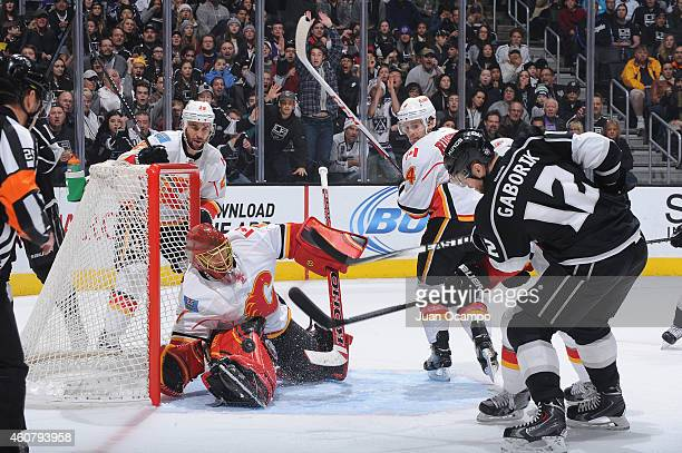 Marian Gaborik of the Los Angeles Kings shoots the puck against Jonas Hiller of the Calgary Flames as Corey Potter and Kris Russell of the Calgary...