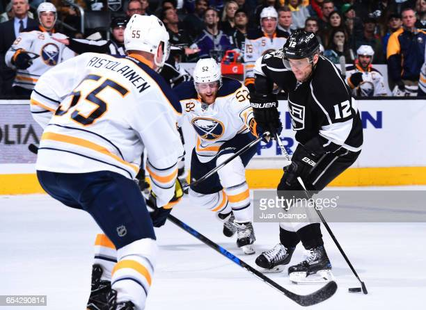 Marian Gaborik of the Los Angeles Kings skates with the puck against Hudson Fasching and Rasmus Ristolainen of the Buffalo Sabres during the game on...