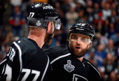 Marian Gaborik of the Los Angeles Kings speaks to teammate Jeff Carter during overtime of Game Two of the 2014 Stanley Cup Final against the New York...