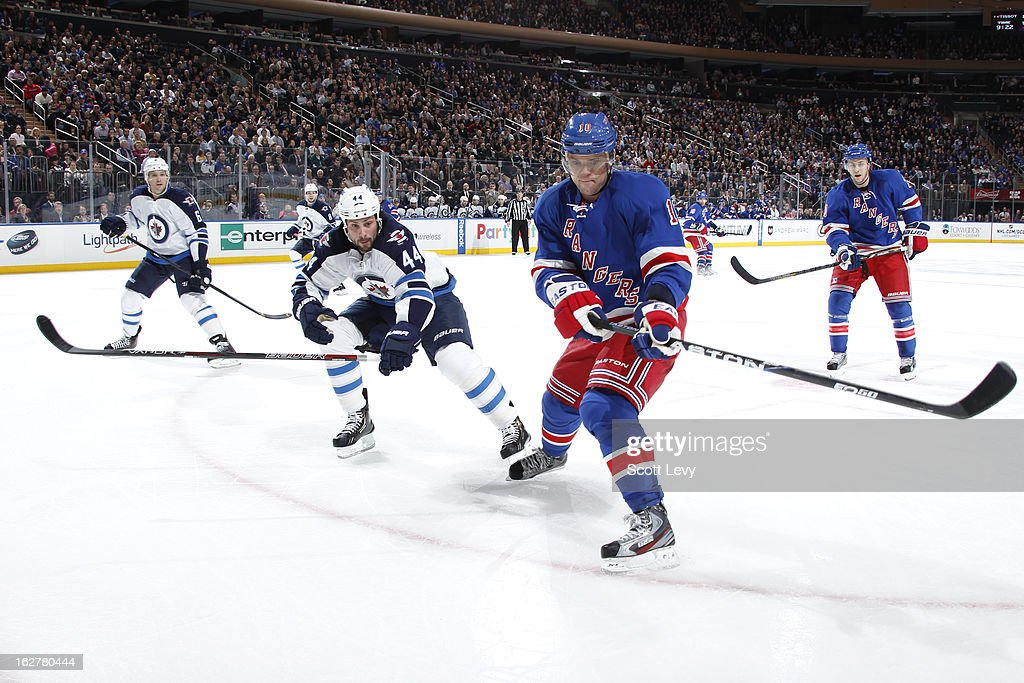 Marian Gaborik #10 of the New York Rangers reaches for the puck under pressure by Zach Bogosian #44 of the Winnipeg Jets at Madison Square Garden on February 26, 2013 in New York City.