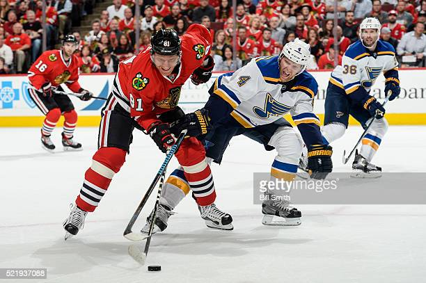 Marian Hossa of the Chicago Blackhawks and Carl Gunnarsson of the St Louis Blues chase the puck in the first period of Game Three of the Western...