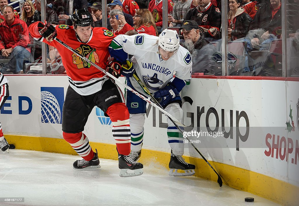 Marian Hossa of the Chicago Blackhawks and David Booth of the Vancouver Canucks chase after the puck during the NHL game on December 20 2013 at the...