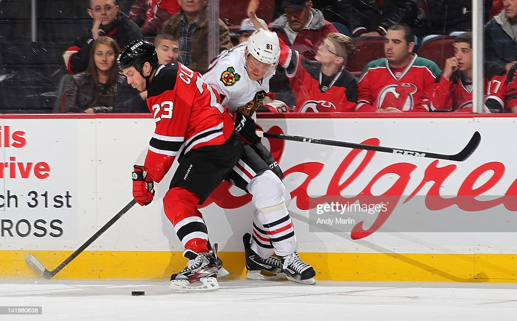 Marian Hossa #81 of the Chicago Blackhawks and David Clarkson #23 of the New Jersey Devils battle for a loose puck during the game at the Prudential Center on March 27, 2012 in Newark, New Jersey.