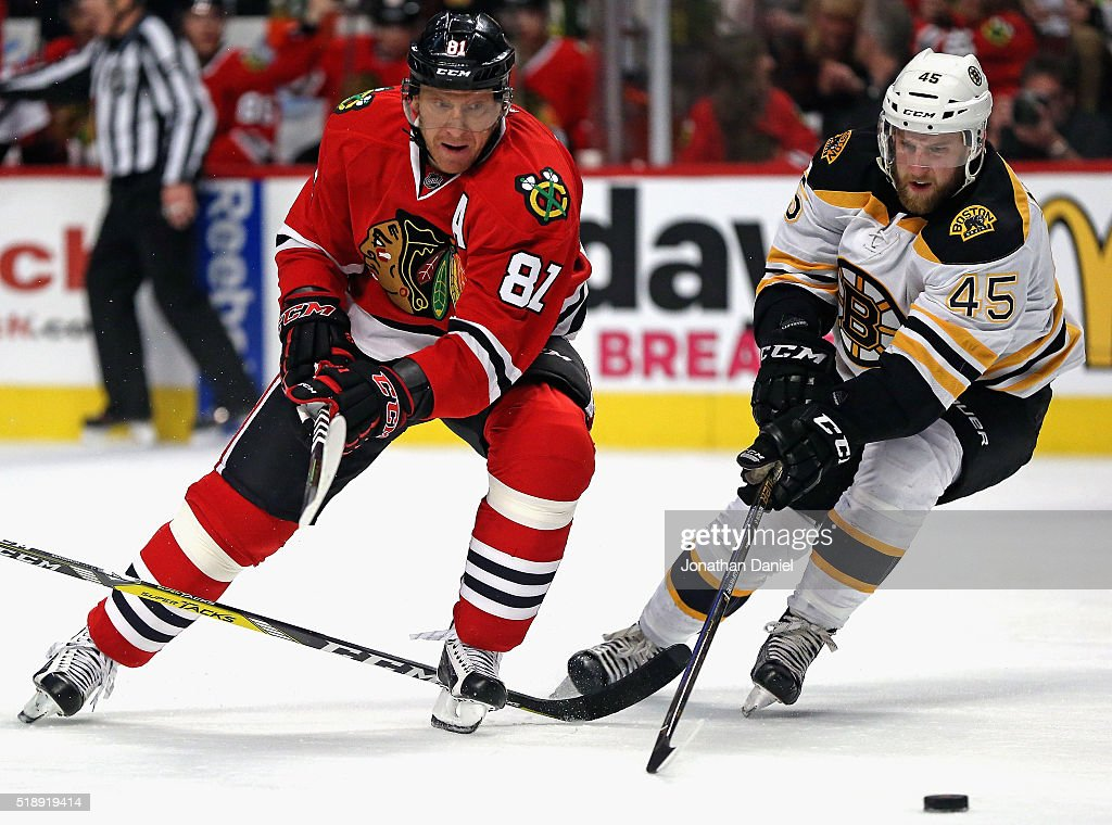 Marian Hossa of the Chicago Blackhawks and Joe Morrow of the Boston Bruins chase the puck at the United Center on April 3 2016 in Chicago Illinois...