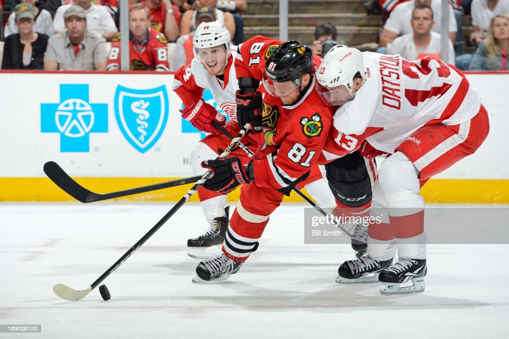 Marian Hossa of the Chicago Blackhawks and Pavel Datsyuk of the Detroit Red Wings battle for the puck as Gustav Nyquist of the Red Wings watches from...