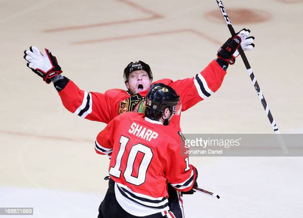 Marian Hossa of the Chicago Blackhawks celebrates a first period goal with teammate Patrick Sharp against the Detroit Red Wings in Game One of the...