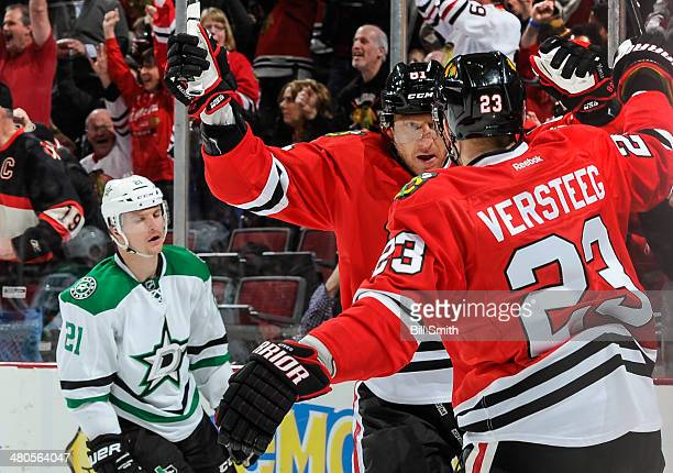 Marian Hossa of the Chicago Blackhawks celebrates with teammate Kris Versteeg after scoring against the Dallas Stars in the second period as Antoine...