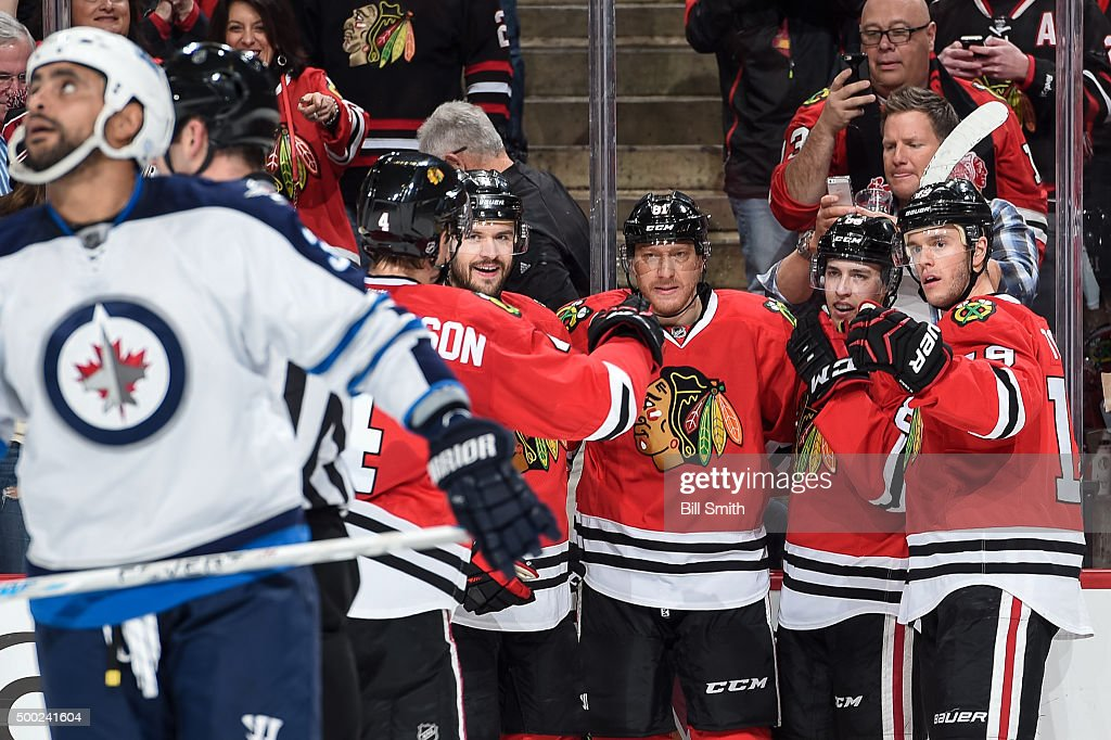 <a gi-track='captionPersonalityLinkClicked' href=/galleries/search?phrase=Marian+Hossa&family=editorial&specificpeople=202233 ng-click='$event.stopPropagation()'>Marian Hossa</a> #81 of the Chicago Blackhawks celebrates with teammates, including <a gi-track='captionPersonalityLinkClicked' href=/galleries/search?phrase=Brent+Seabrook&family=editorial&specificpeople=638862 ng-click='$event.stopPropagation()'>Brent Seabrook</a> #7, Teuvo Teravainen #86 and <a gi-track='captionPersonalityLinkClicked' href=/galleries/search?phrase=Jonathan+Toews&family=editorial&specificpeople=537799 ng-click='$event.stopPropagation()'>Jonathan Toews</a> #19, after scoring against the Winnipeg Jets in the first period of the NHL game at the United Center on December 6, 2015 in Chicago, Illinois.