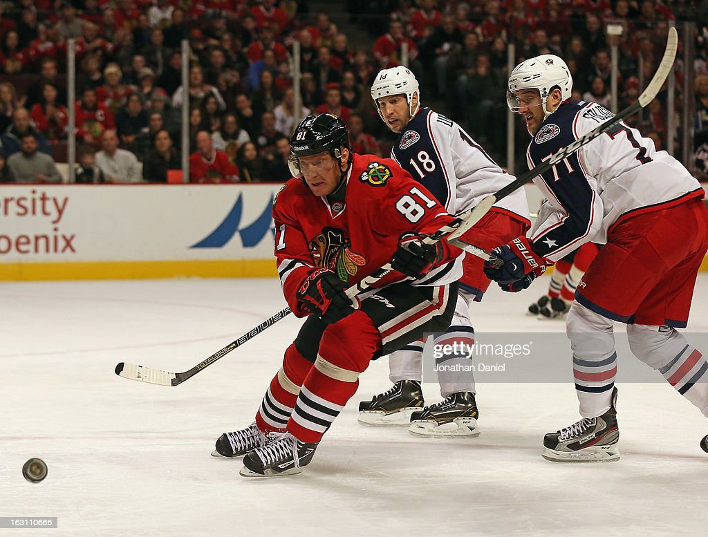 <a gi-track='captionPersonalityLinkClicked' href=/galleries/search?phrase=Marian+Hossa&family=editorial&specificpeople=202233 ng-click='$event.stopPropagation()'>Marian Hossa</a> #81 of the Chicago Blackhawks chases the puck in front of <a gi-track='captionPersonalityLinkClicked' href=/galleries/search?phrase=R.J.+Umberger&family=editorial&specificpeople=636608 ng-click='$event.stopPropagation()'>R.J. Umberger</a> #18 and <a gi-track='captionPersonalityLinkClicked' href=/galleries/search?phrase=Nick+Foligno&family=editorial&specificpeople=537821 ng-click='$event.stopPropagation()'>Nick Foligno</a> #71 of the Columbus Blue Jackets at the United Center on March 1, 2013 in Chicago, Illinois. The Blackhawks defeated the Blue Jackets 4-3 in overtime.