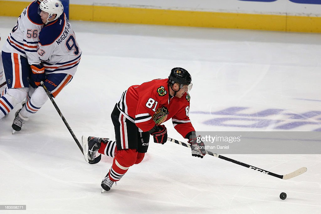 <a gi-track='captionPersonalityLinkClicked' href=/galleries/search?phrase=Marian+Hossa&family=editorial&specificpeople=202233 ng-click='$event.stopPropagation()'>Marian Hossa</a> #81 of the Chicago Blackhawks controls the puck as <a gi-track='captionPersonalityLinkClicked' href=/galleries/search?phrase=Teemu+Hartikainen&family=editorial&specificpeople=5485386 ng-click='$event.stopPropagation()'>Teemu Hartikainen</a> #56 and <a gi-track='captionPersonalityLinkClicked' href=/galleries/search?phrase=Ryan+Nugent-Hopkins&family=editorial&specificpeople=7144190 ng-click='$event.stopPropagation()'>Ryan Nugent-Hopkins</a> #93 of the Edmonton Oilers collide at the United Center on March 10, 2013 in Chicago, Illinois. The Oilers defeated the Blackhawks 6-5.