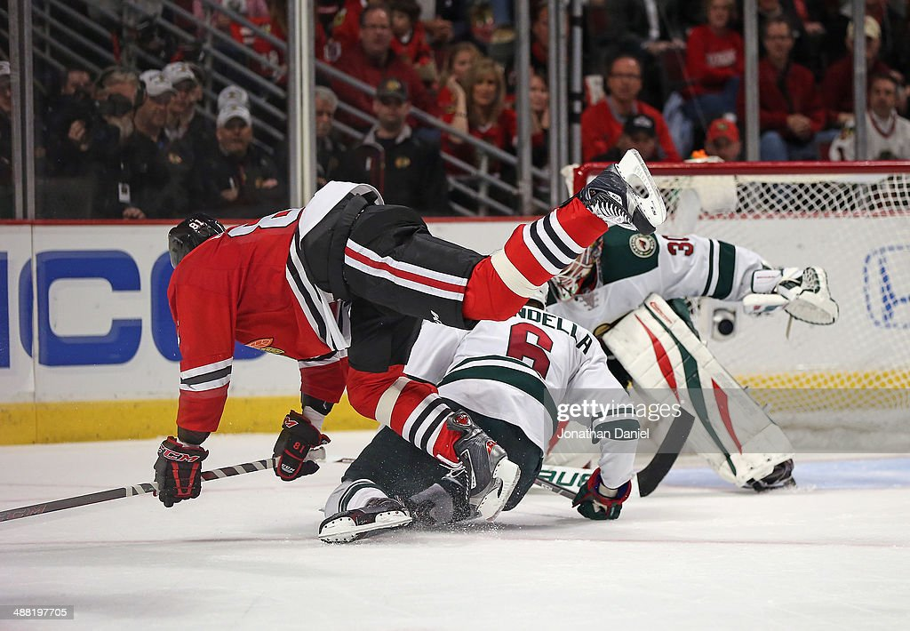 Marian Hossa #81 of the Chicago Blackhawks falls over Marco Scandella #6 of the Minnesota Wild in Game Two of the Second Round of the 2014 NHL Stanley Cup Playoffs at the United Center on May 4, 2014 in Chicago, Illinois. The Blackhawks defeated the Wild 4-1.