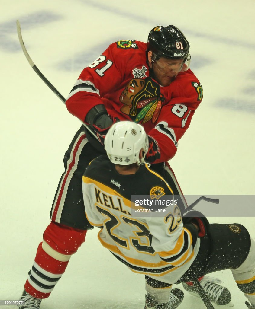 Marian Hossa #81 of the Chicago Blackhawks hits Chirs Kelly #23 of the Boston Bruins during Game One of the 2013 NHL Stanley Cup Finals at United Center on June 12, 2013 in Chicago, Illinois. The Blackhawks defeated the Bruins 4-3 in triple overtime.
