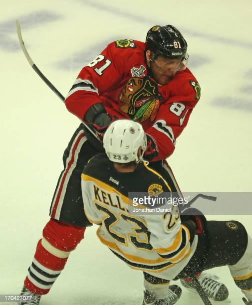 Marian Hossa of the Chicago Blackhawks hits Chirs Kelly of the Boston Bruins during Game One of the 2013 NHL Stanley Cup Finals at United Center on...