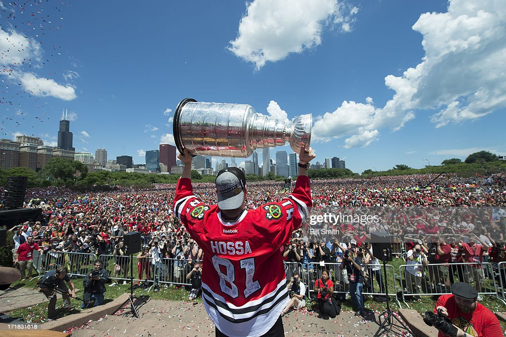 Marian Hossa #81 of the Chicago Blackhawks holds up the Stanley Cup trophy to the crowd in Grant Park during the Blackhawks Victory Parade and Rally on June 28, 2013 in Chicago, Illinois.