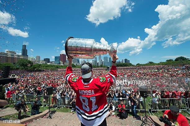 Marian Hossa of the Chicago Blackhawks holds up the Stanley Cup trophy to the crowd in Grant Park during the Blackhawks Victory Parade and Rally on...