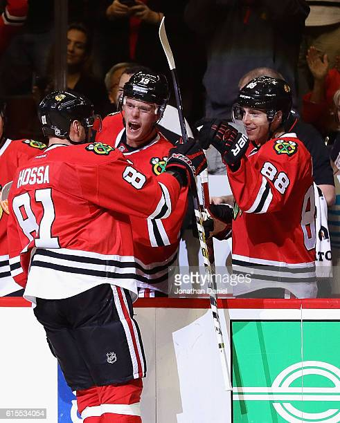 Marian Hossa of the Chicago Blackhawks is greeted by teammates Jonathan Toews and Patrick Kane after scoring his 500th career goal against the...