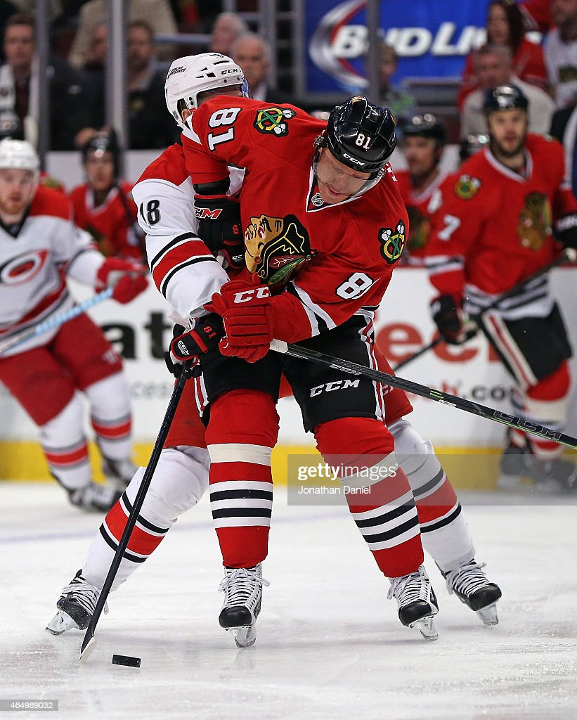 Marian Hossa #81 of the Chicago Blackhawks is harrased by Jay McClement #18 of the Carolina Hurricanes at the United Center on March 2, 2015 in Chicago, Illinois.