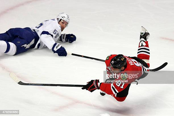Marian Hossa of the Chicago Blackhawks takes a shot as he is tripped by Braydon Coburn of the Tampa Bay Lightning in the first period during Game...