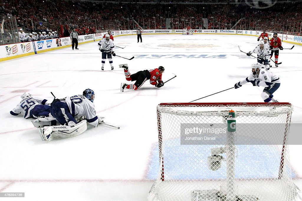 Marian Hossa #81 of the Chicago Blackhawks takes a shot as he is tripped by Braydon Coburn #55 of the Tampa Bay Lightning in the first period during Game Three of the 2015 NHL Stanley Cup Final at the United Center on June 8, 2015 in Chicago, Illinois.