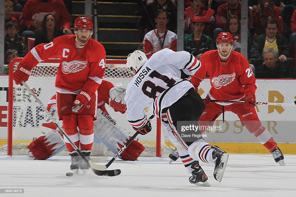 Marian Hossa #81 of the Chicago Blackhawks takes a slap shot between Henrik Zetterberg #40 and Brian Lashoff #23 of the Detroit Red Wings during an NHL game at Joe Louis Arena on March 3, 2013 in Detroit, Michigan. Chicago won 2-1 in a shoot-out