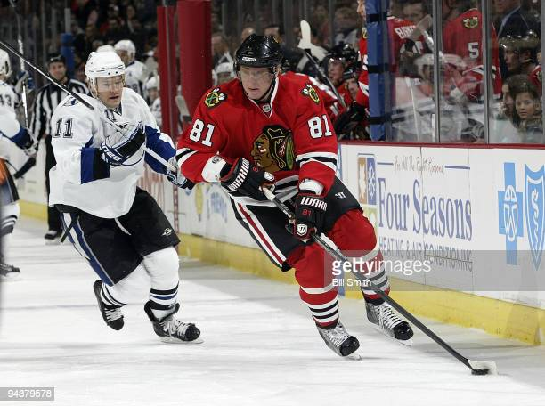 Marian Hossa of the Chicago Blackhawks takes the puck up the boards as Jeff Halpern of the Tampa Bay Lightning follows behind on December 13 2009 at...