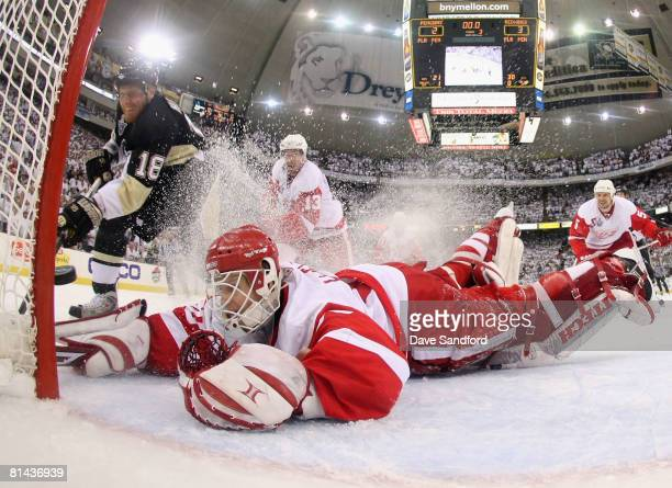 Marian Hossa of the Pittsburgh Penguins slides the puck through the crease past goaltender Chris Osgood of the Detroit Red Wings in the final seconds...