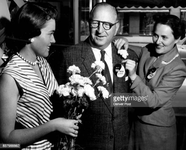 Marian Little and her sister Joanne pin a Colorado carnation on William E Glass in the course of giving 3000 posies to women who visited Cottrell's...