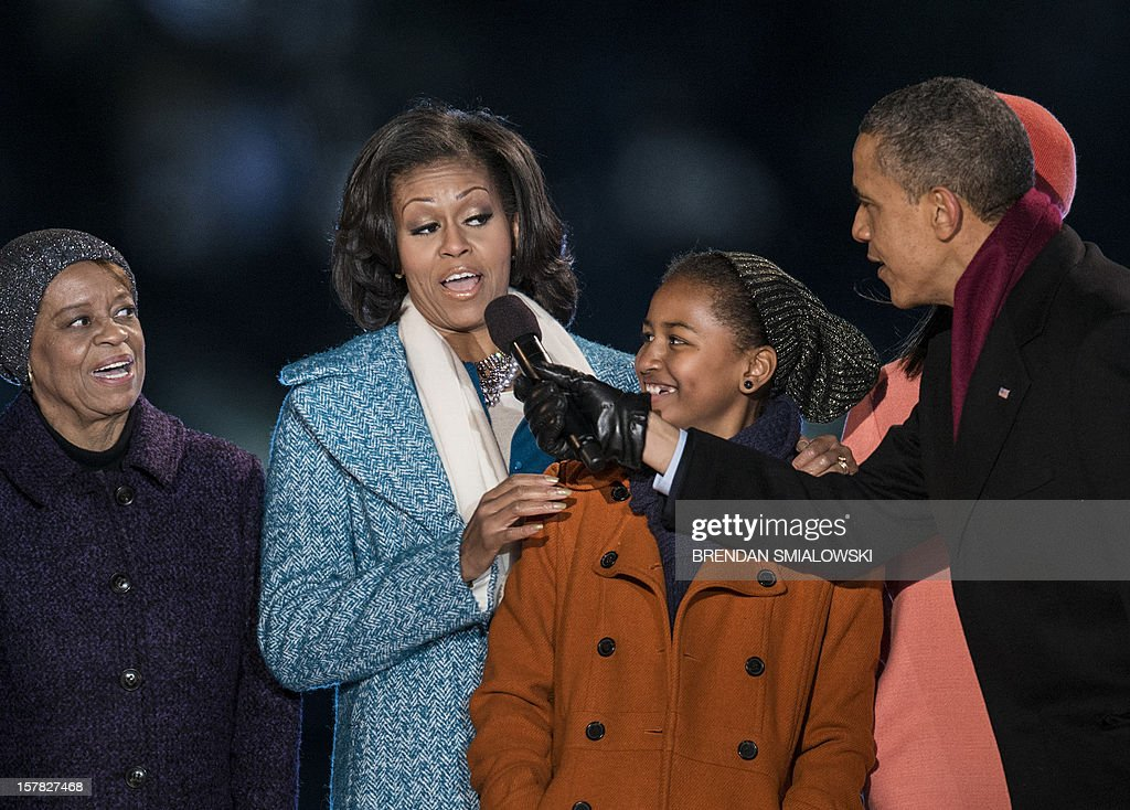 Marian Robinson (L) and Sasha Obama (2R) watch as US President Barack Obama points a microphone toward US first lady Michelle Obama while singing Santa Clause is Coming to Town during the 90th annual National Christmas Tree Lighting on the Ellipse of the National Mall December 6, 2012 in Washington, DC. Obama and others attended the event which included entertainment before the lighting of the National Christmas Tree. AFP PHOTO/Brendan SMIALOWSKI