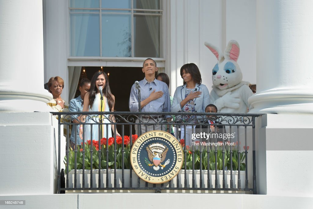 Marian Robinson, left, stands next to her granddaughter, Sasha Obama, face partly showing, as Jessica Sanchez sings the National anthem as President Barack Obama stands next to his wife, Michelle Obama, 'Kid President', Robbie Novak, and the Easter Bunny during the annual White House Easter Egg Roll on Monday April 01, 2013 in Washington, DC.