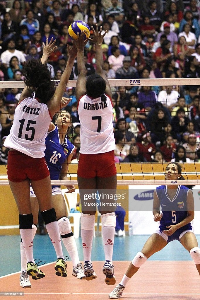 Mariangel Perez (C) of Venezuela plays the ball against Karla Ortiz (L) and Andrea Urrutia of Venezuela during a match between Peru and Venezuela in women's volleyball as part of the XVII Bolivarian Games Trujillo 2013 at Coliseo gran Chimu on November 29, 2013 in Trujillo, Peru.